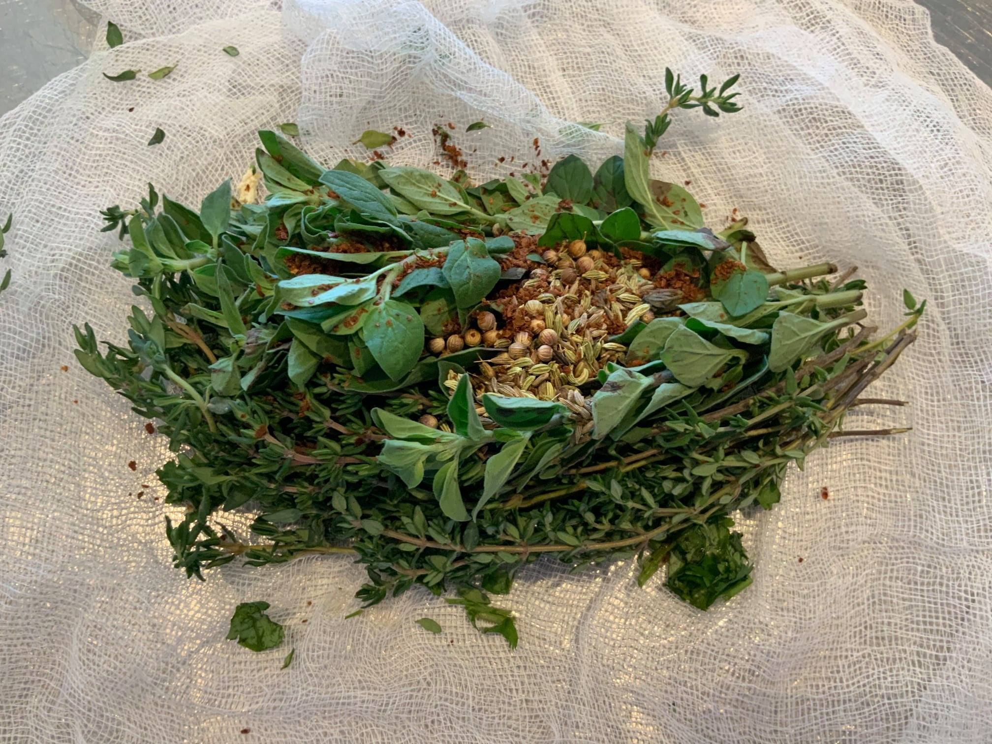 green herbs and roasted spices sit on cheesecloth